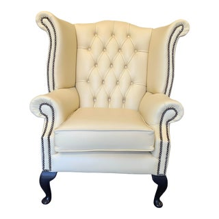 Vintage Mid-Century English Leather Chesterfield Wingback Chair and Footstool, Parchment, a Set For Sale