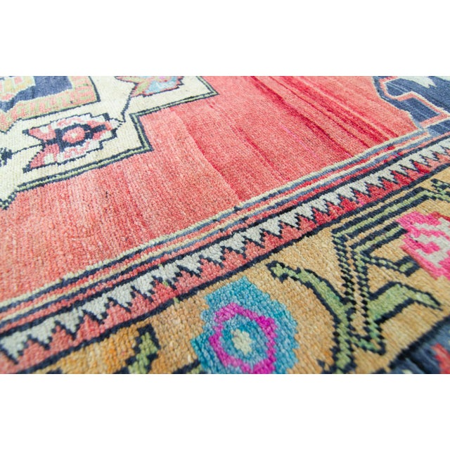 A geometrically patterned vintage rug with a large medallion as its focal point, intermingling with floral interest....