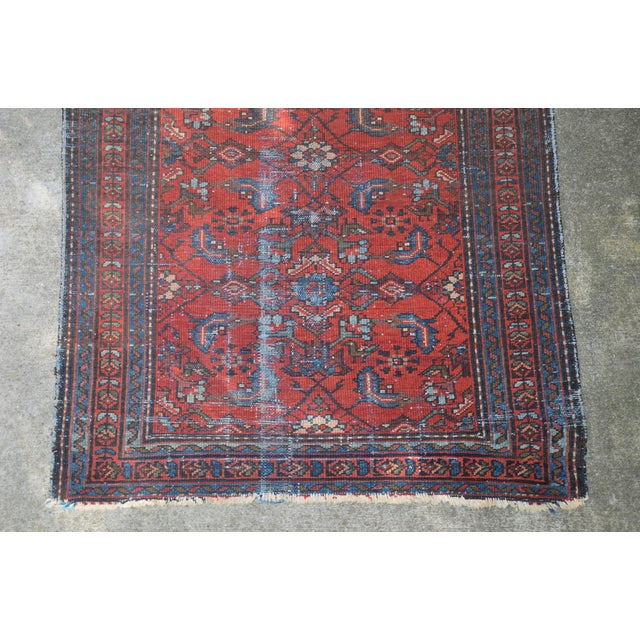 An antique flat woven Persian rug in brick red and navy blue. This rug has multiple borders and an all over floral design...