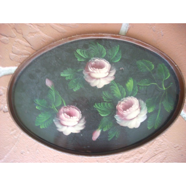 Three large pink cabbage roses with green foliage hand painted on an oval black background; brown painted rim and back;...