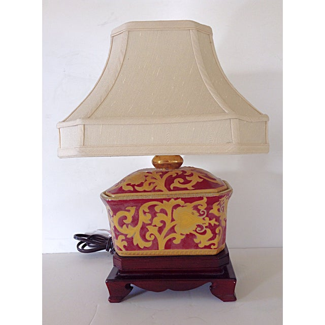 Small Asian porcelain lamp on wood stand with silk shade that is lined. Uses 3-way. 150 watt max. type A bulb