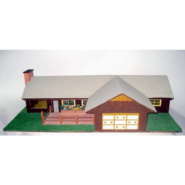 Hand crafted, large ranch-style dollhouse made in the 1970s. The front of the house has a fenced in faux brick pathway and...