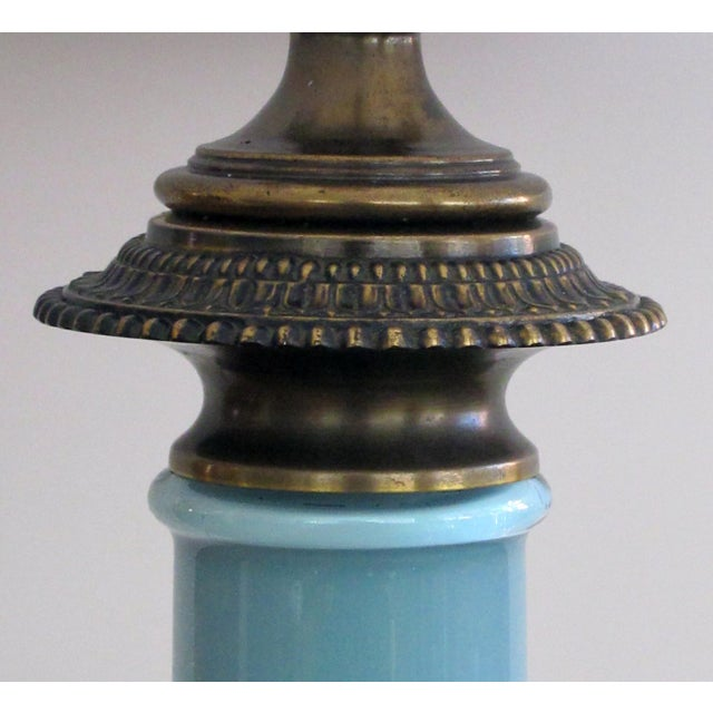 each cased-glass column with brass capital and base all resting on a black marble base