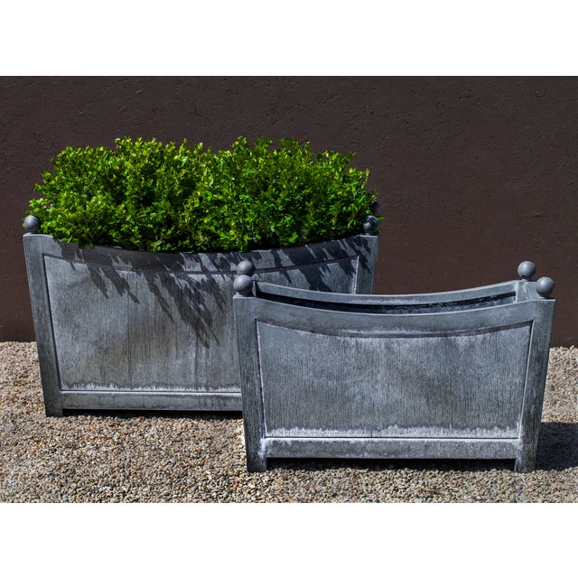 A square planter made of Zinc coated Steel with tapered sides.