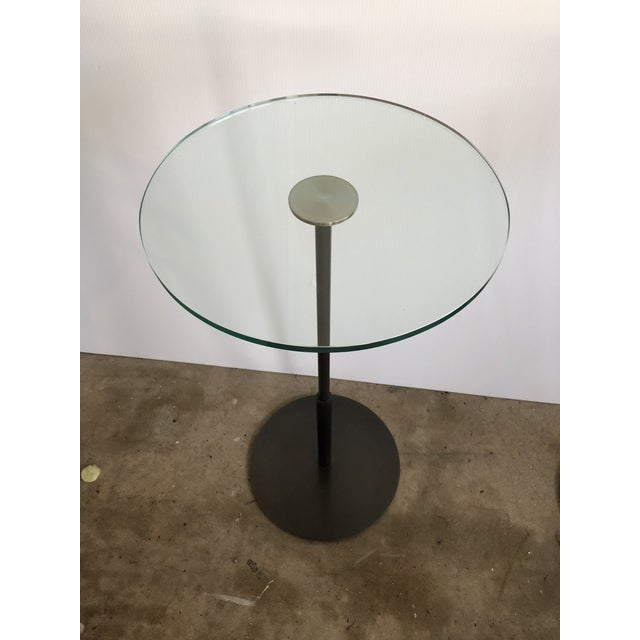 This is a pair of cocktail tables from the late 20th century. The pieces feature dark bronze finishes over steel.