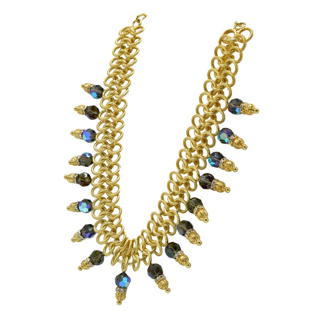 Italian runway necklace in gold leaf metal and blue stones by Justin Joy. Contains Jaipur stones.