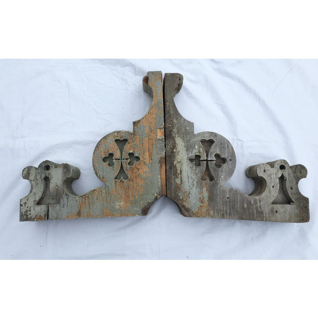 Pair of weathered wooden corbels. Wear consistent with age, chipped wood, paint loss.