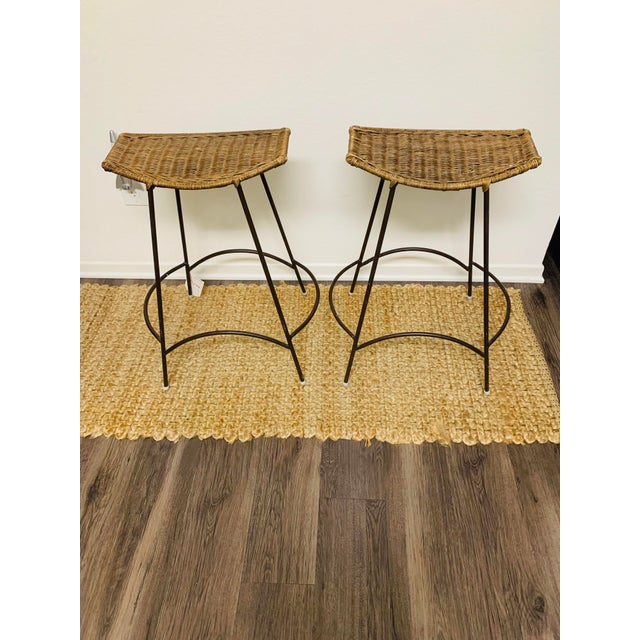 Mid-Century Modern Wrought Iron and Wicker Rattan Bar Stools by Arthur Umanoff - a Pair These bar height stools are...