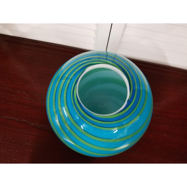 Art deco style blue glass vase with green swirls. It is in very good condition.