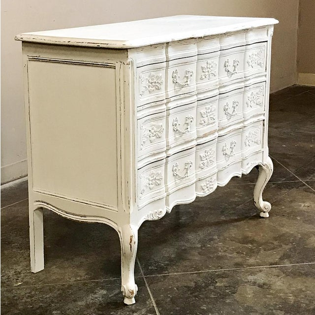 Antique Country French Provincial Painted Commode features a contoured and carved facade fitted with brass pulls, enhanced...
