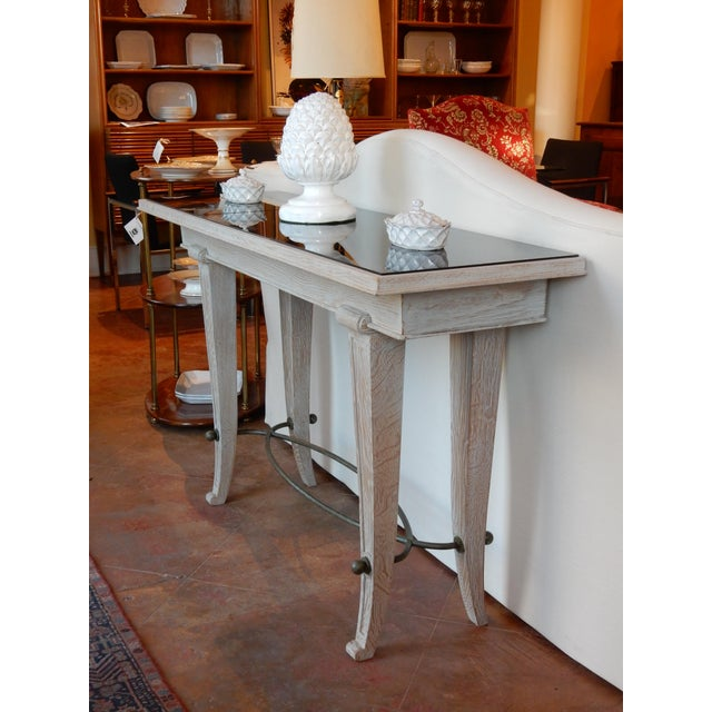 Unusual 1930's-1940's cerused oak console with black glass top and patinaed iron stretcher. Black glass is in 3 squares.