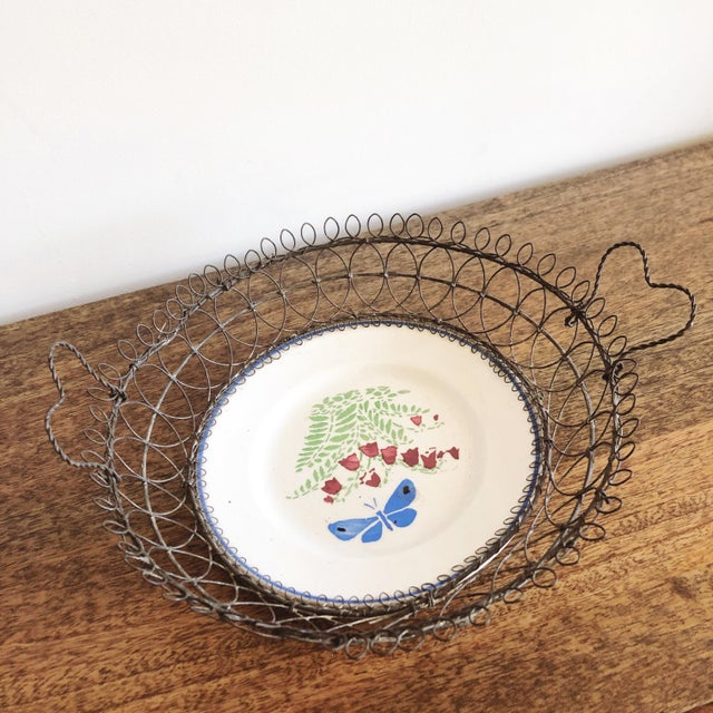 Antique Majolica ceramic plate enclosed in metal wire basket with heart handles dating from early 1900's or late 1800's....