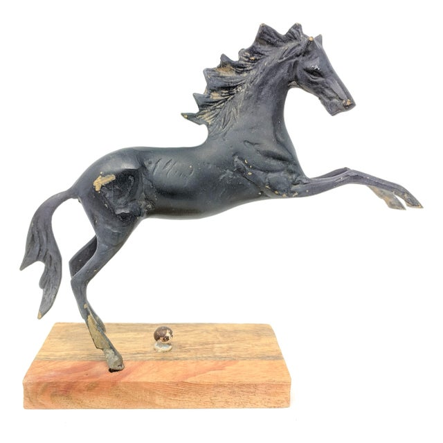 Vintage metal horse statue, mounted on wooden base. A dynamic piece, with very slight hints of abstraction.