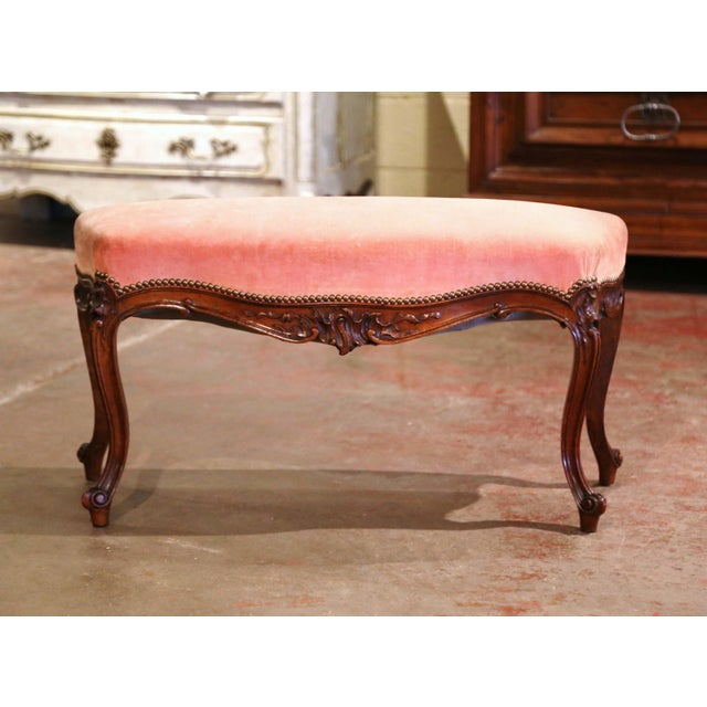 Crafted in Provence, France circa 1960, the antique fruitwood piano bench stands on cabriole legs decorated with floral...