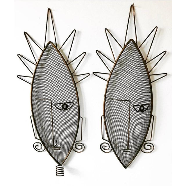 Very rare pair of wire mesh masks sculptures by Frederic Weinberg. Interesting African influence in the design....