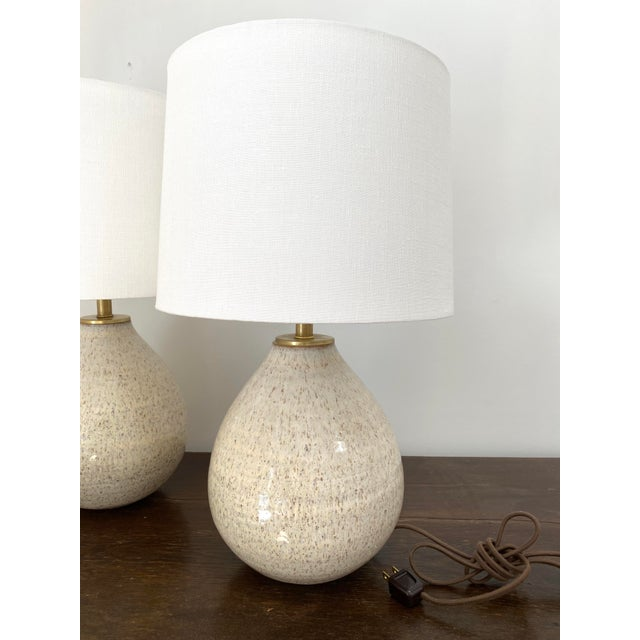 Fantastic pair of handmade ceramic lamps in an ivory gloss glaze with brown speckling. Beautiful, versatile color and...