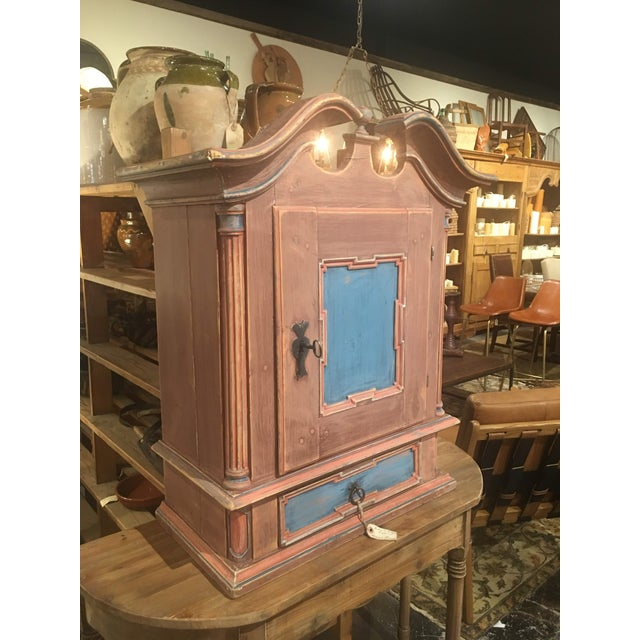 This Antique Swedish polychrome hanging cabinet, from the 19th century, features it's original hardware. The crown molding...
