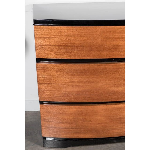 A streamlined Art Deco low chest by modern age furniture company in mahogany and black lacquer with a bow fronted design....