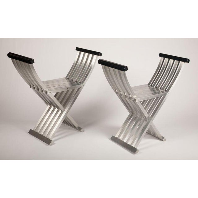 A pair of folding chair benches in brushed aluminum designed with precision engineering for a sleek look and finely...