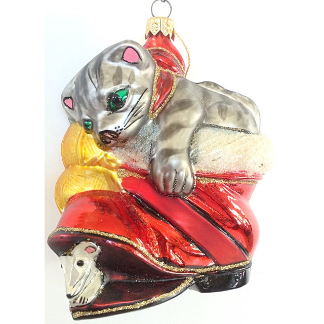 European hand made limited edition of Christopher Radko's design of a cat playing with a mouse in Santa's boot is made of...