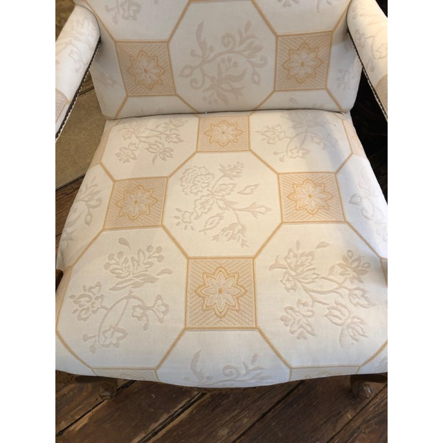 Roomy and classic French style carved light wood club chair by Baker having neutral beige and white geometric upholstery.