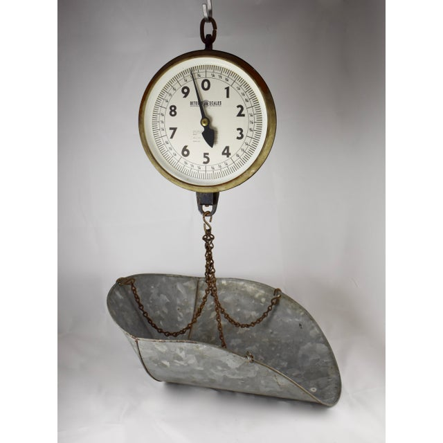 A vintage hanging mercantile produce scale along with a galvanized steel scoop, circa 1930-40. The scale is made by...