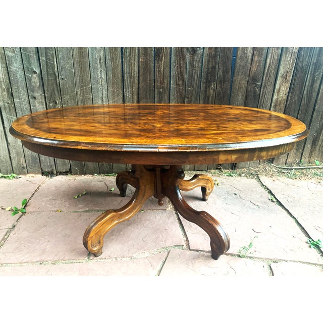 Antique oval coffee table features burled walnut veneer. Other wood veneer was used to decorate the edge of the oval top....