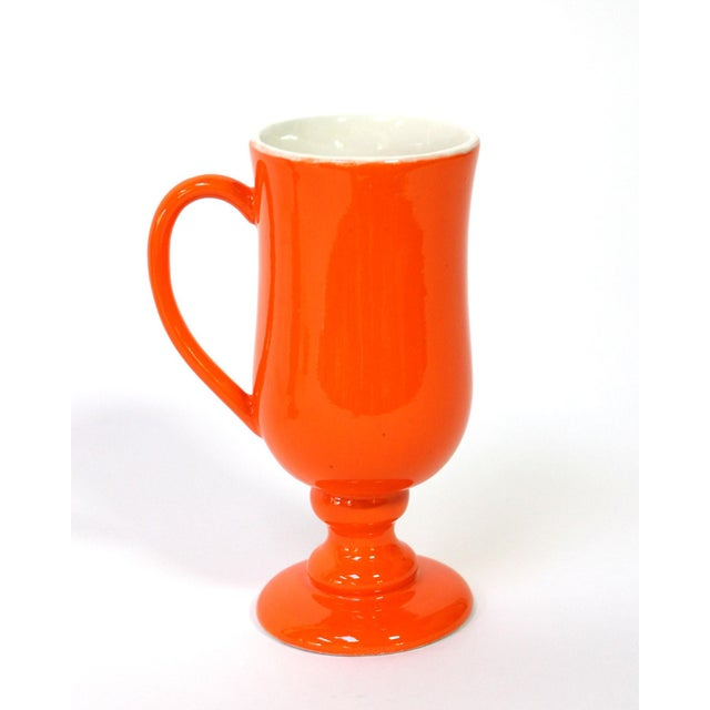"These vintage ceramic mugs with handles and pedestals are glazed a vibrant ""Hermès"" orange on the outsides and an antique..."