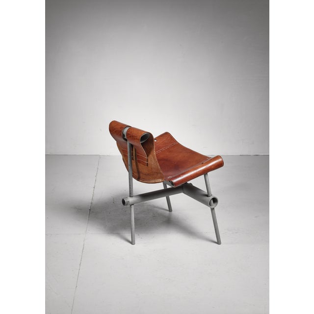 A low prototype lounge chair attributed to Max Gottschalk. The chair is made of metal pipes and thick brown leather.