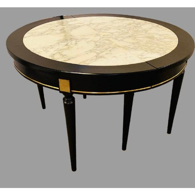 French Hollywood Regency Jansen style ebony center or dining table having a Carrara white gray veined marble top with two...