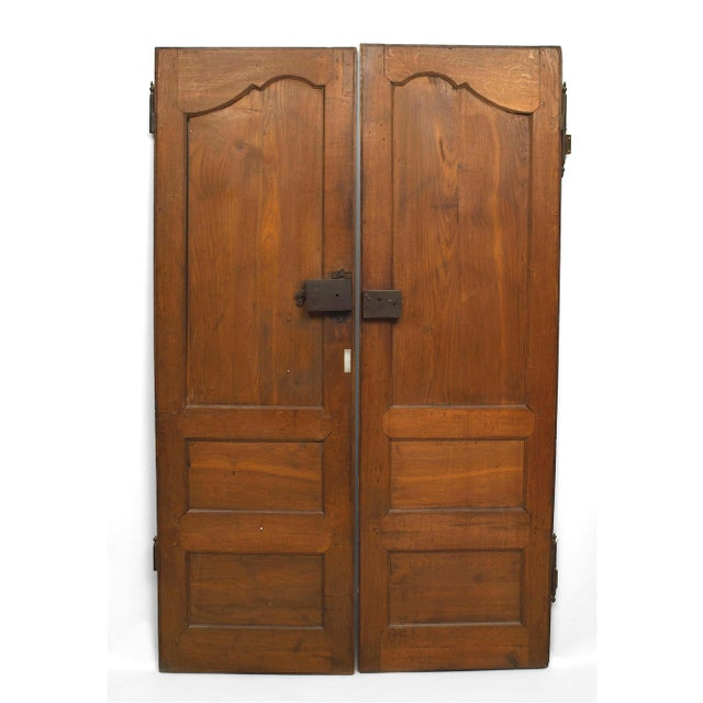 Pair of 18th century French Provincial walnut doors, each carved with two small rectangular panels beneath a larger one....