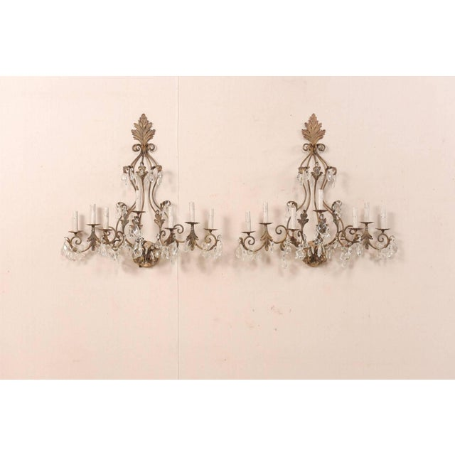 A pair of French crystal seven-light sconces from the mid-20th century. This pair of generously-sized, midcentury, French...