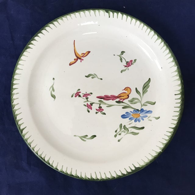 Vintage French faience plates festooned with green borders and bird and flower motif. Illegible maker's mark on the back....