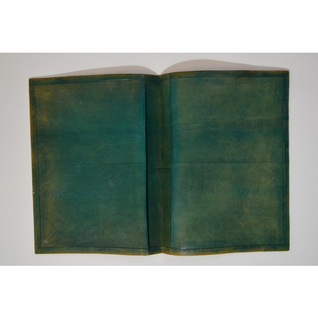 This leather portfolio was purchased in an antique shop in Manhattan. The antique piece has interior pockets and is...