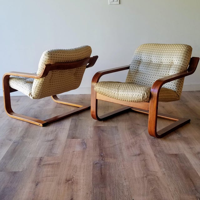 A pair of Norwegian bentwood teak lounge chairs made by Westnofa. These chairs feature a bentwood frame creating a...