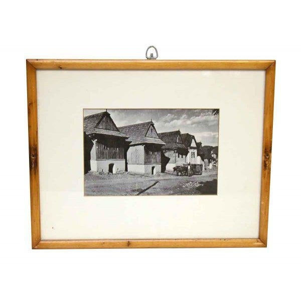 Pine frame and creme matting with a black and white photo of a row of old farm style houses.