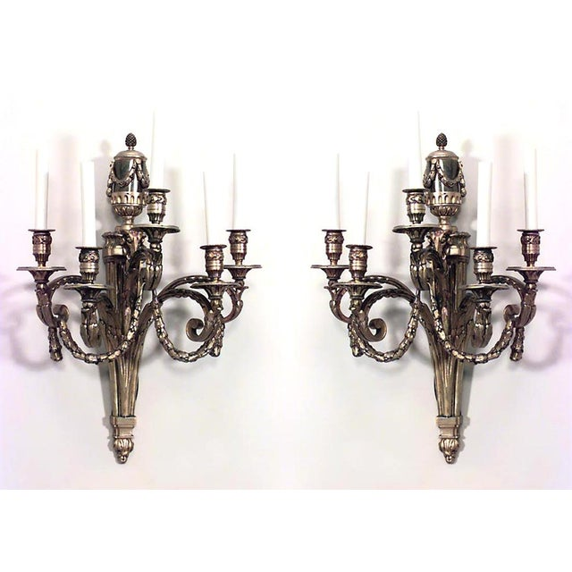 Pair of French Louis XVI style (19th-20th century) bronze doré five-arm wall sconces with festoon design and finial top...