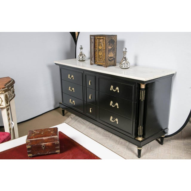 A French Louis XVI style marble-top ebonized dresser or sideboard by Maison Jansen. This finely detailed chest commode has...