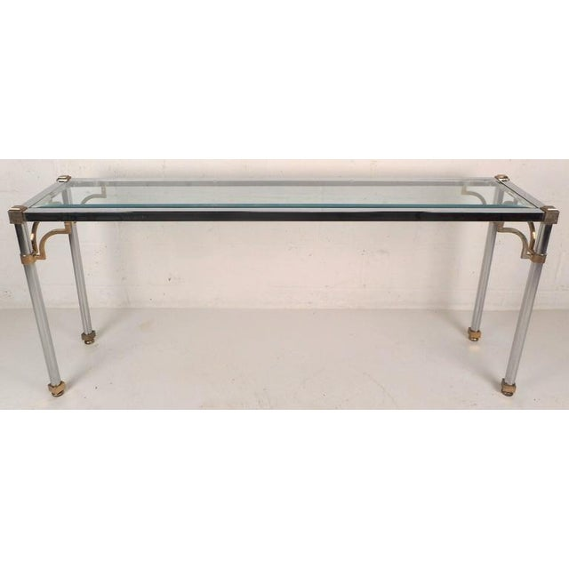 This stunning vintage modern console table features a heavy chrome frame with brass accents on each corner and on all four...