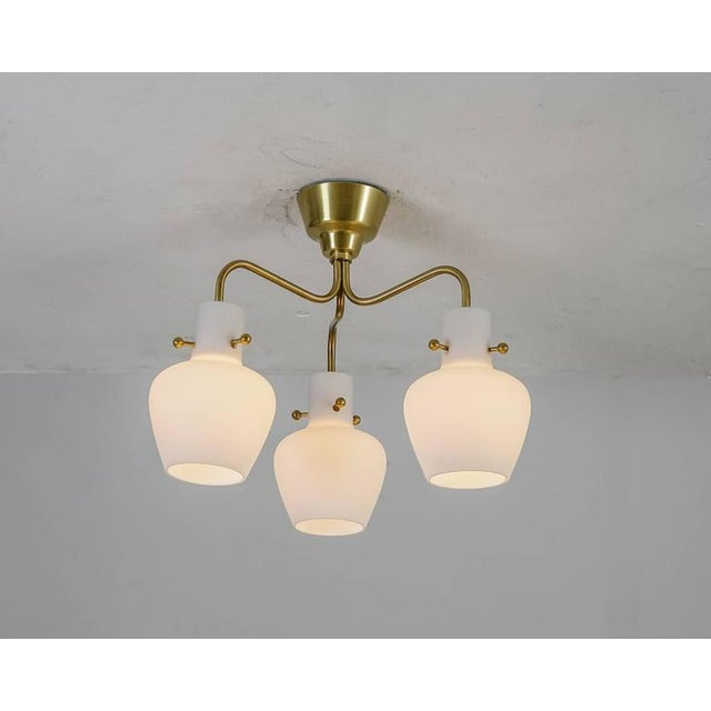 A three shaded flushmount chandelier by Hans Bergström for Ateljé Lyktan, Sweden, 1940s The lamp is made of three brass...