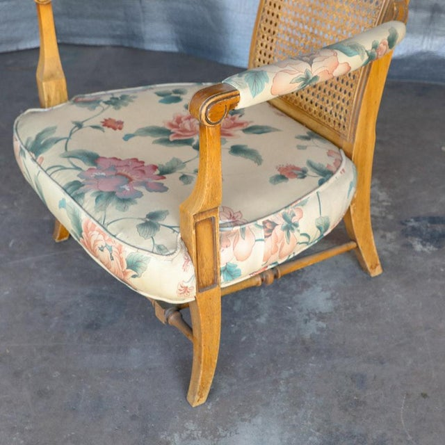 A rare and unusual oversized vintage cane back armchair with floral print cushions. The chair has a tall back with caning,...