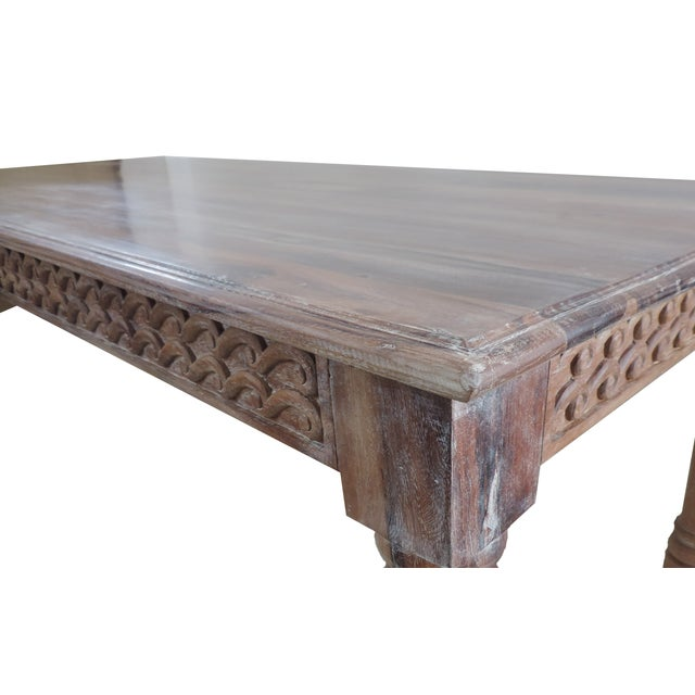 An Anglo table made of reclaimed teak wood, featuring round, scroll carvings adorning the table's skirt. All finished with...
