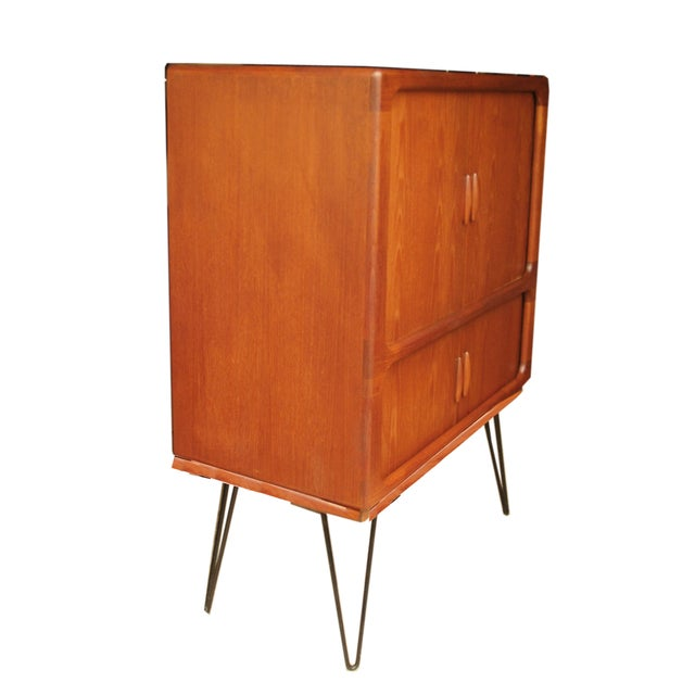Gorgeous Mid-Century Modern teak cabinet by Dyrlund. Comes with tambour doors and multiple storage compartments. This...