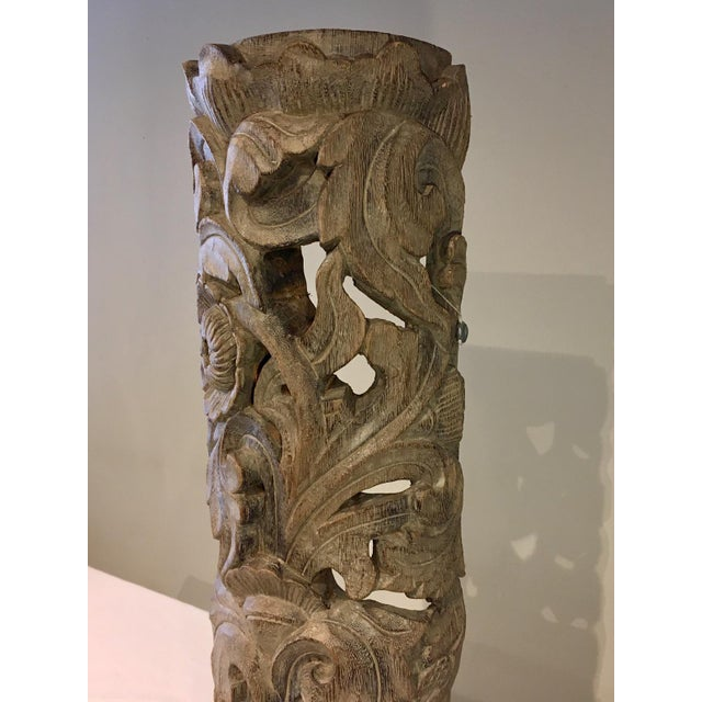 Hand carved floral totem wooden sculpture with an aged patina. The piece is from the 1990s.