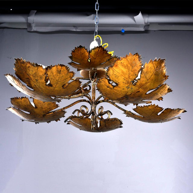 Mid-century Spanish five light hanging fixture features two tiers of intricately rendered metal leaves with gilded finish....