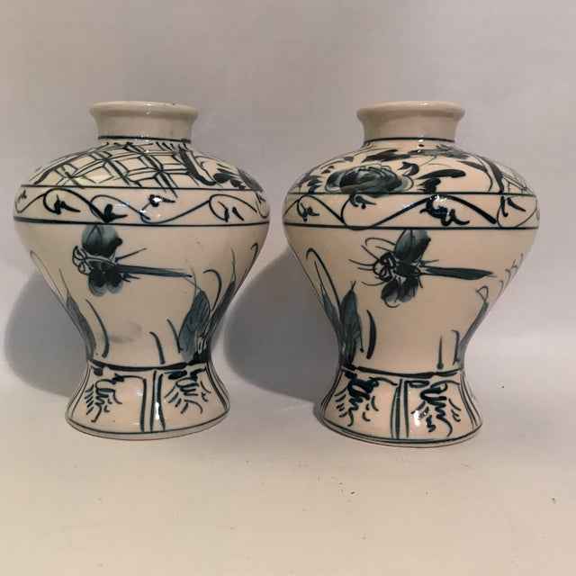 Pair of white ceramic baluster form vases with hand painted blue decoration including flowers and dragonflies. Unusual...