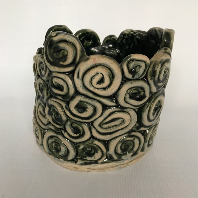 Vintage pottery cachepot made from stacked swirls with green glaze.