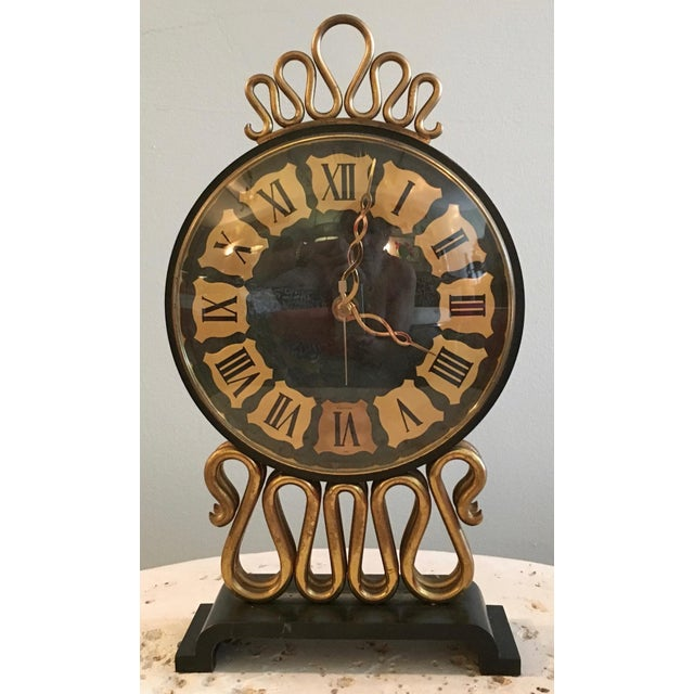This is a great mid-century table clock by Bulova. The body is metal. It is run on battery.
