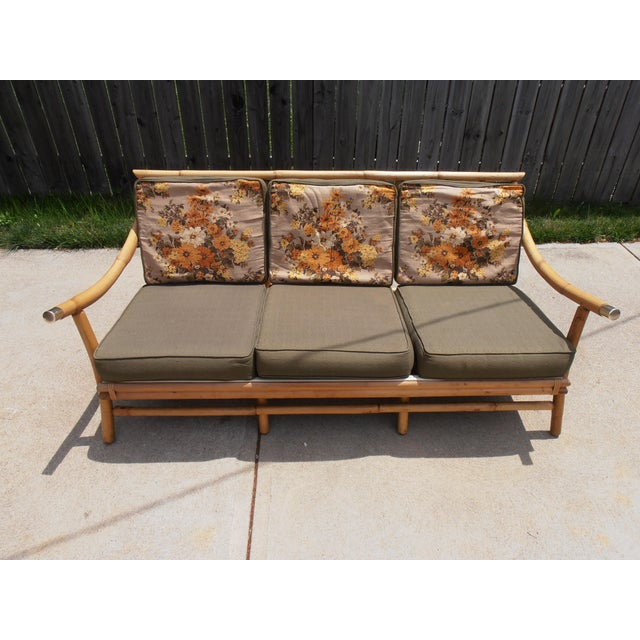 Vintage bamboo sofa with gold accent caps and upswept arm rests. Original cushions. Fabric is in very good condition,...