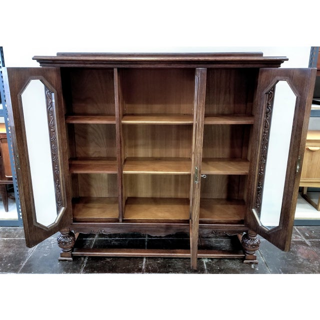 French glazed bookcase of carved oak wood in the Renaissance style. Made in Belgium circa the 1920s. Medium-dark oak...